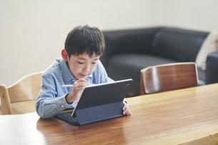 リビングでタブレットPCを見ながら勉強する男の子の写真素材 [FYI04856506]