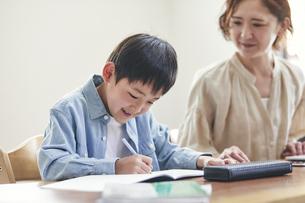 リビングで勉強する男の子とノートパソコンを使う女性の写真素材 [FYI04856508]