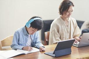 リビングで勉強する男の子とノートパソコンを使う女性の写真素材 [FYI04856510]