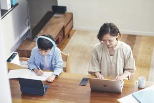 リビングで勉強する男の子とノートパソコンを使う女性の写真素材 [FYI04856511]