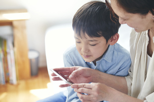 部屋でスマートフォンを見る女性と男の子の写真素材 [FYI04856512]