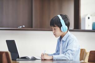 リビングでタブレットPCを見ながら勉強する男の子の写真素材 [FYI04856513]