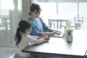 テレワークをする女性と話しかける子供の写真素材 [FYI04856534]