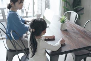 テレワークをする女性と話しかける子供の写真素材 [FYI04856535]