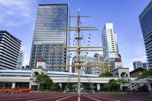 船の帆柱(マスト)を中心に置いた東京湾沿いの竹芝埠頭公園から浜松町駅にかけて開発の続くビル群の写真素材 [FYI04856596]
