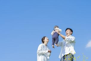 青空のもと、赤ちゃんを高く抱き上げる父母の写真素材 [FYI04857274]