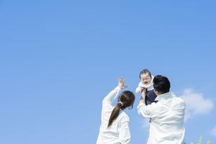 青空のもと、赤ちゃんを高く抱き上げる父母の写真素材 [FYI04857281]