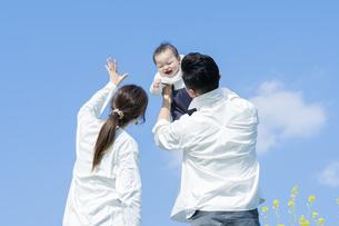 青空のもと、赤ちゃんを高く抱き上げる父母の写真素材 [FYI04857283]