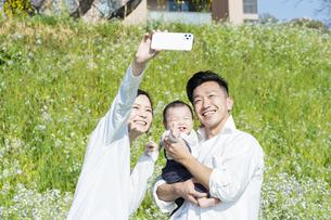 屋外で記念撮影をする親子の写真素材 [FYI04857291]