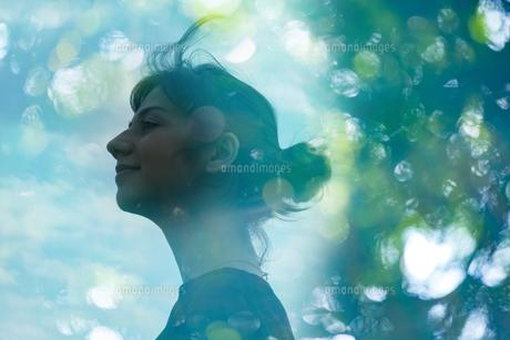 エコロジーイメージ・女性の横顔とアウトフォーカスで撮影した森の合成CGの写真素材 [FYI04857336]