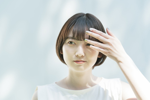 髪を整える女性と、白壁に映る木々の影の写真素材 [FYI04857343]
