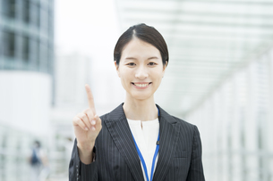 人差し指を立てるアジア人の若いビジネスウーマンの写真素材 [FYI04857400]