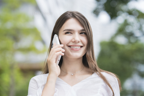 スマートフォンで通話する女性の写真素材 [FYI04857403]