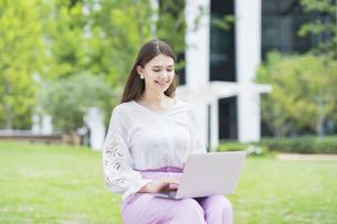 屋外でノートパソコンを操作する女性の写真素材 [FYI04857408]