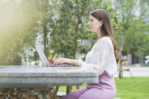 屋外でノートパソコンを操作する女性の写真素材 [FYI04857413]