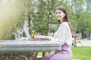 屋外でノートパソコンを操作する女性の写真素材 [FYI04857414]
