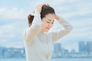 両手で髪を整える女性の写真素材 [FYI04858017]