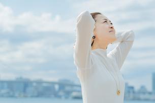 両手で髪を整える女性の写真素材 [FYI04858018]
