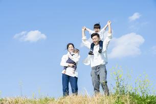 青空のもと、笑顔で歩く親子4人の写真素材 [FYI04858071]