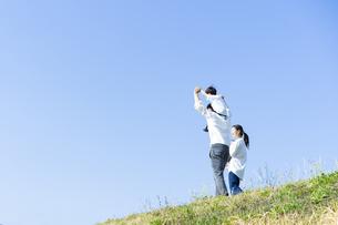 青空のもと、笑顔で歩く親子4人の写真素材 [FYI04858073]