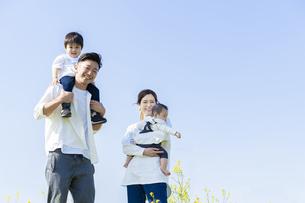 青空のもと、笑顔で歩く親子4人の写真素材 [FYI04858080]
