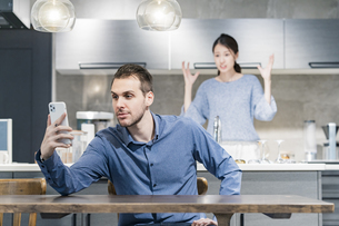 スマートフォンを操作する男性と、怒る女性の写真素材 [FYI04858627]