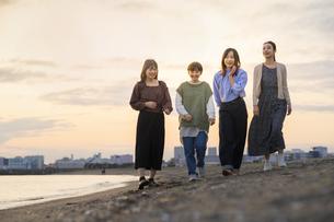 夕暮れの中、寄り添って海沿いを歩く女性4人の写真素材 [FYI04858895]