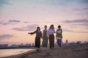 夕暮れの中、寄り添って海沿いを歩く女性4人の写真素材 [FYI04858897]