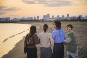 夕暮れの中、寄り添って海沿いを歩く女性4人の写真素材 [FYI04858915]