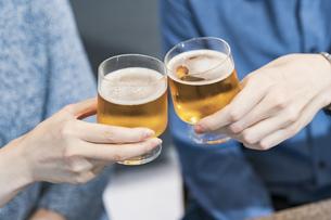 ビールで乾杯する若い男女の写真素材 [FYI04858971]
