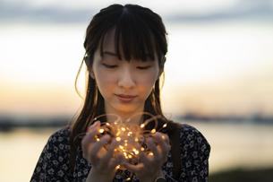 イルミネーションライトを両手で包む若い女性の写真素材 [FYI04858975]