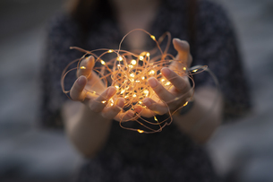 イルミネーションライトを両手で包む若い女性の写真素材 [FYI04858977]