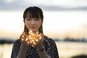 イルミネーションライトを両手で包む若い女性の写真素材 [FYI04858979]