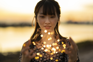 イルミネーションライトを両手で包む若い女性の写真素材 [FYI04858982]