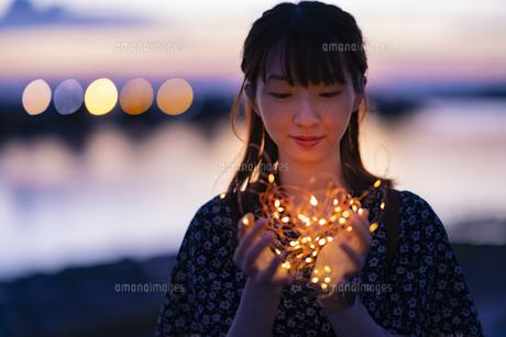 イルミネーションライトを両手で包む若い女性の写真素材 [FYI04858985]