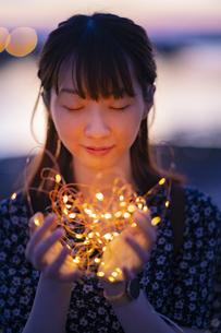 イルミネーションライトを両手で包む若い女性の写真素材 [FYI04858988]