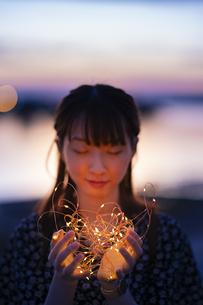 イルミネーションライトを両手で包む若い女性の写真素材 [FYI04858991]