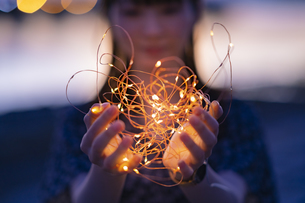 イルミネーションライトを両手で包む若い女性の写真素材 [FYI04858994]
