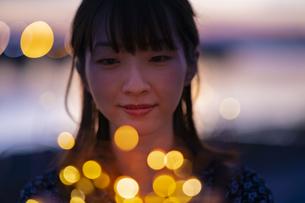 イルミネーションライトを両手で包む若い女性の写真素材 [FYI04858997]