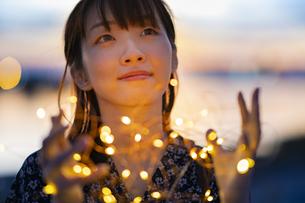 イルミネーションライトを両手で包む若い女性の写真素材 [FYI04859001]
