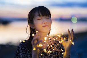 イルミネーションライトを両手で包む若い女性の写真素材 [FYI04859004]