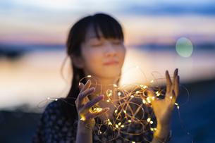 イルミネーションライトを両手で包む若い女性の写真素材 [FYI04859008]