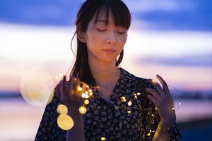 イルミネーションライトを両手で包む若い女性の写真素材 [FYI04859012]