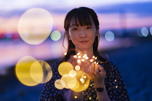 イルミネーションライトを両手で包む若い女性の写真素材 [FYI04859016]