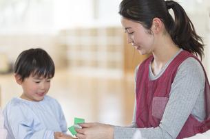折り紙を折る保育士と園児の写真素材 [FYI04859023]