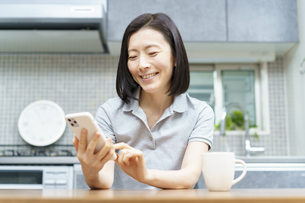 室内でスマートフォンを操作する女性の写真素材 [FYI04859240]