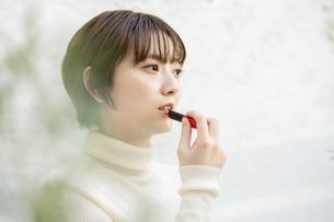 口紅を塗るアジア人の若い女性の写真素材 [FYI04859253]