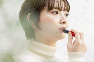 口紅を塗るアジア人の若い女性の写真素材 [FYI04859254]
