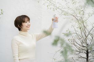 植物に水を吹き付ける女性の写真素材 [FYI04859255]