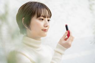口紅を塗るアジア人の若い女性の写真素材 [FYI04859271]